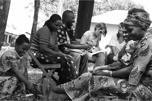 Women's Emancipation and Development Agency (WOMEDA) Executive Director Juma Massisi (seated, center) facilitates conversation among women and Amizade students in Kayanga, Tanzania, as part of research that supported a successful United States Agency for International Development grant award for WOMEDA.